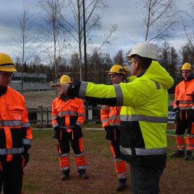 Läraren Johan Sulkakoski instruerar eleverna på Optimas byggnadslinje.