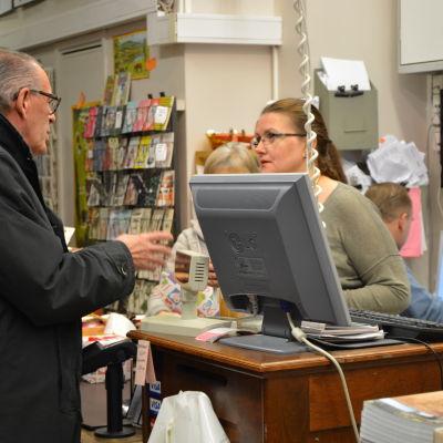 Anna-Lena Palomäki betjänar en kund vid kassan på Gros bokhandel