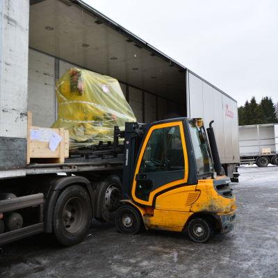 En gaffeltruck lossar en av Piccolos lastbilar.
