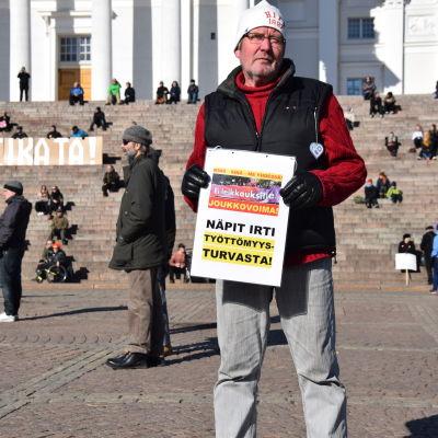 Ilkka Merikukka protesterar mot att de fattiga drabbas hårdast av regeringens nedskärningspolitik.