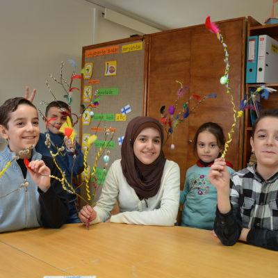 Syriska elever i Taalintehtaan koulu med påskris i handen.