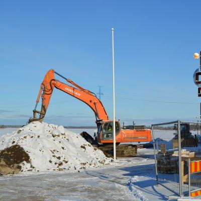 Grävmaskin arbetar på kajen nedanför Tullhuset i Inre hamnen i Vasa.