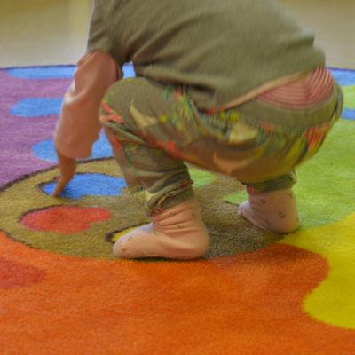 Ett litet barn leker på en färggrann matta.