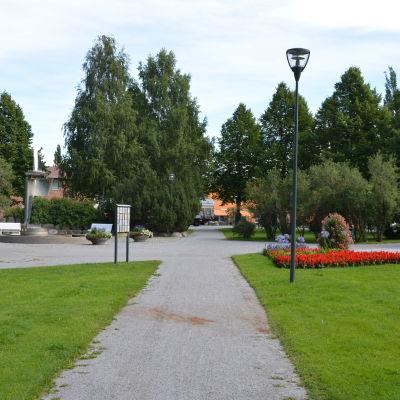 En somrig bild av Brändö torg med blomrabatter till höger och en fontän till vänster.