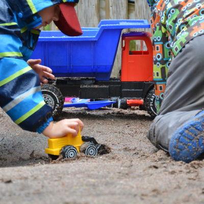Barnen leker i sanden med leksaker.