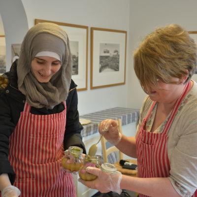 Ayaa Sheikh Jalal och Maria Pick fyller på honungsburkar.