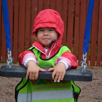 En liten flicka står vid gungan vid daghemmet Touhula i Borgå