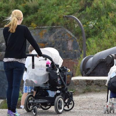 mamma med små barn intill gamla kanoner på Sveaborg.