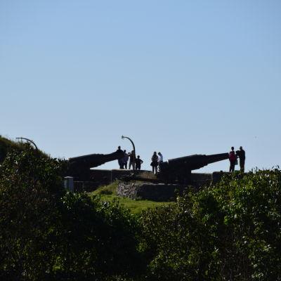 Silhuetter av turister som fotograferar sig själva intill kanoner uppe på en kulle (Gustavssvärd på Sveaborg).