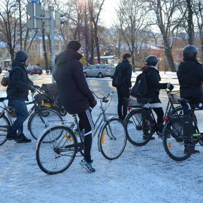 Ett gäng cyklister står vid trafikljuset i centrala Åbo.