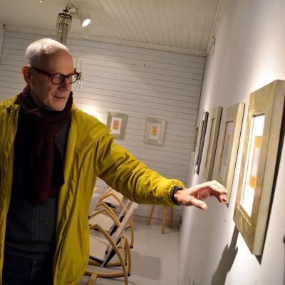 Konstnär framför sina verk