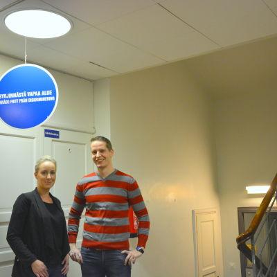 Heidi Svartsjö och Jukka Mäntymaa poserar under skylt om diskriminering.