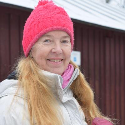 kvinna i röd luva framför trävägg