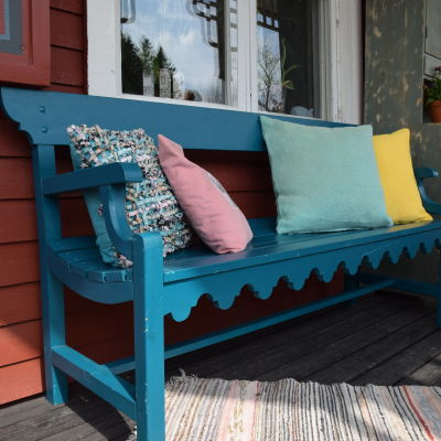 Turkos bänk med ryggstöd på Strömsös veranda.
