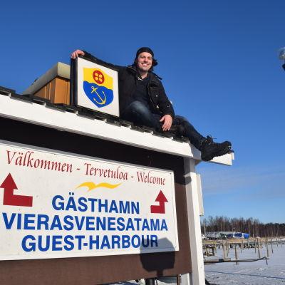 Benjamin Lundin har klättrat upp på en välkomstskylt i Ingå.