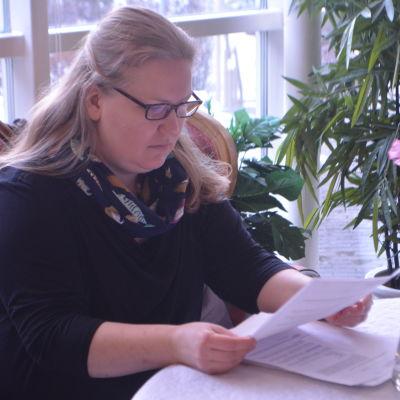 En kvinna sitter vid ett bord och läser koncentrerat ett papper. Framför henne på bordet ligger fler papper.