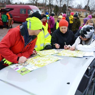 Frivilliga vid kartor som de delar upp i områden som de ska leta efter Harry Karjalainen på.