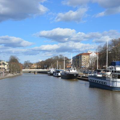 Vy över Aura å från Teaterbron, med restaurangbåtar i förgrunden.