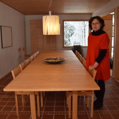 En kvinna klädd i rött och svart och med röda glasögons tår vid ett långt köksbord. Hon heter Karin Widnäs.