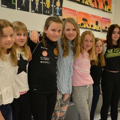Sju flickor med armarna om varandra.