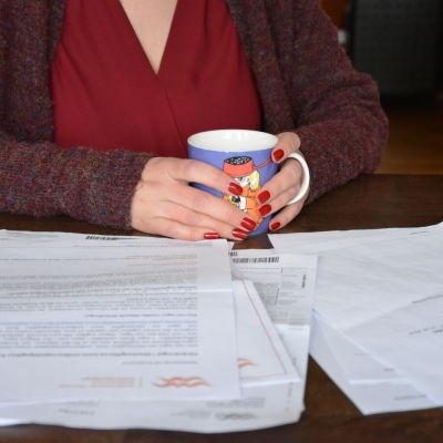 """""""Maria"""" med högen av dokument som har att göra med barnens dagvårdsavgift."""