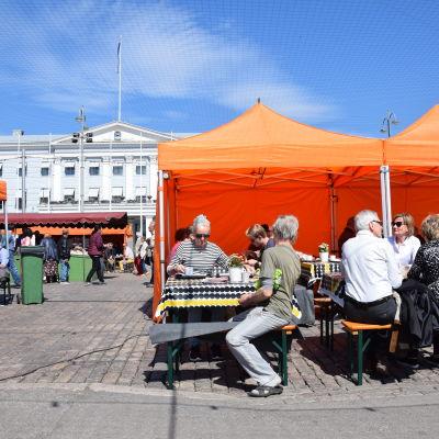 Folk sitter och dricker kaffe vid torgcafét på Salutorget. I bakgrunden syns stadshuset.