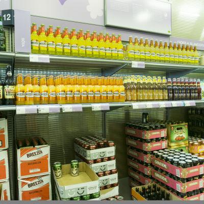 Alkoholdrycker på hyllor i matbutik.
