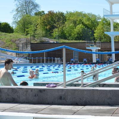 Människor som simmar i en utebassäng.
