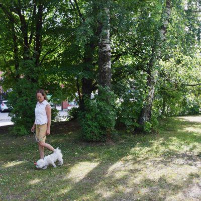 Kvinna i topp och shorts går i en grön park tillsammans med sin hund. Bakom buskarna och träden skymtar höghus.