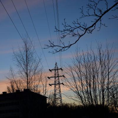 Kraftledning i gryningsljus över hustak.