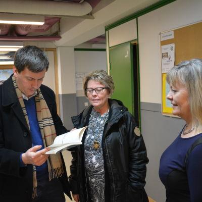 Andreas von Bergmann, Marika Eklund och rektor Annika Gustafsson bläddrar i Pargas svenska gymnasiums historik.
