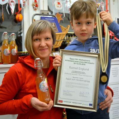 Gunnel och hennes son Joakim håller i glöggen, medaljen och diplomet.