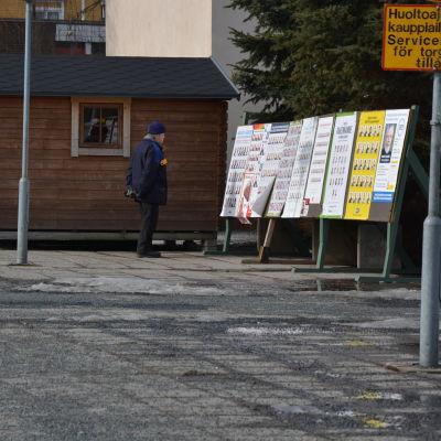 Äldre man står och tittar på valaffischer på Karleby torg.