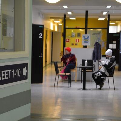 Folk väntar på sin tur inne i hälsostationen.