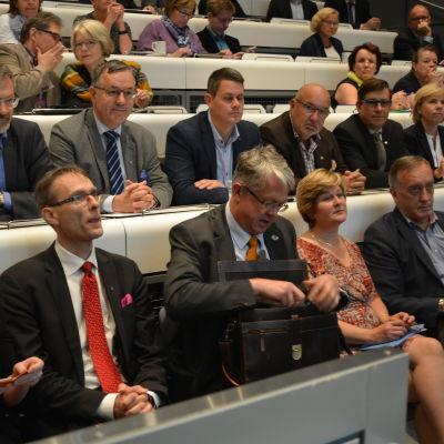 Understatssekreterare Tuomas Pöysti och minister Juha Rehula på främsta raden.