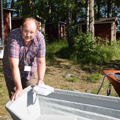 Thomas Skarpman lutar mot en roddbåt och visar upp en registreringsuppmaning.