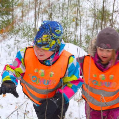 Två barn springer upp för en snötäckt backe.
