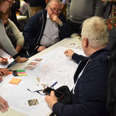 Människor sitter samlade runt en karta på ett bord.