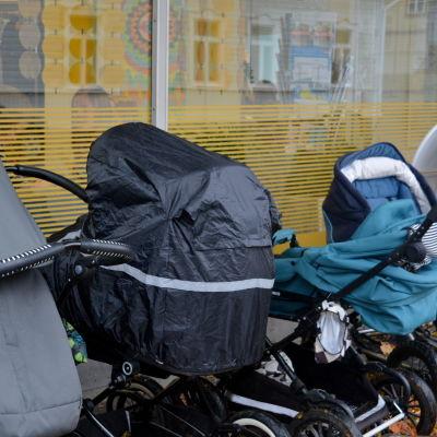 Barnvagnar står på rad ute