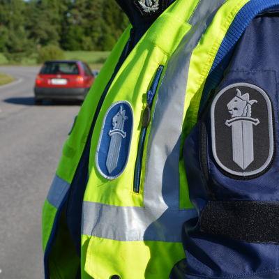 Polis står intill väg.