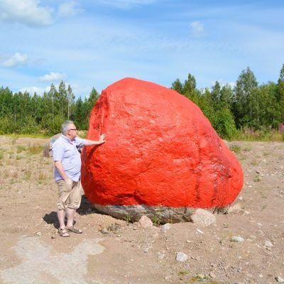 Ole Tjeder intill den första stenen som målades röd.