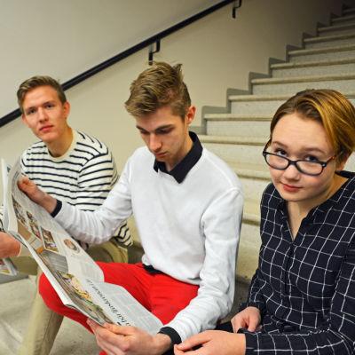 Gymnasieeleverna Fabian Tillander, Kristofer Söderström och Pinja Karlqvist läser tidningen Östnyland