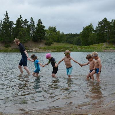 Simskolebarnen går i vattnet hand i hand.