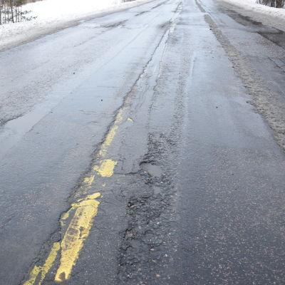 En asfalterad väg med skador i beläggningen.