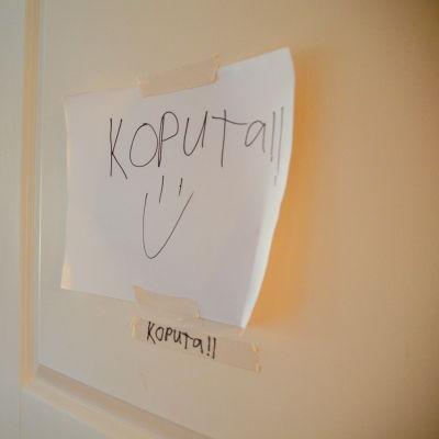 papperslapp med texten koputa på en dörr