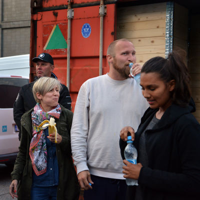 Alla ute ur containern, dricker vatten och mumsar på bananer.