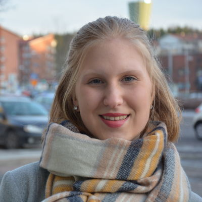 Ung kvinna med tjock halsduk utomhus.