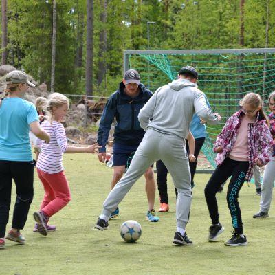 Richard och Fredrik Jensen spelar fotboll med Vårberga skolas elever.