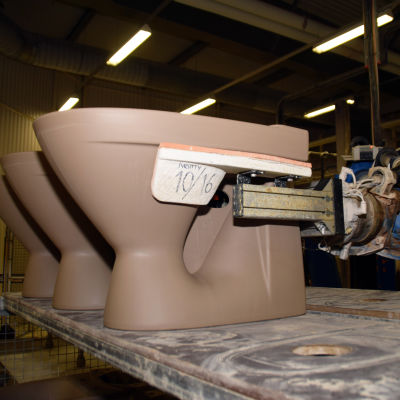 En blå robotarm placerar en wc-stol på ett bord i Ido badrums fabrik.