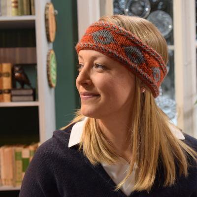 En kvinna, Elin Skagersten-Ström, som är fotograferad i profil i ett vardagsrum. Hon småler lite och bär ett stickat pannband med gråa lador på.